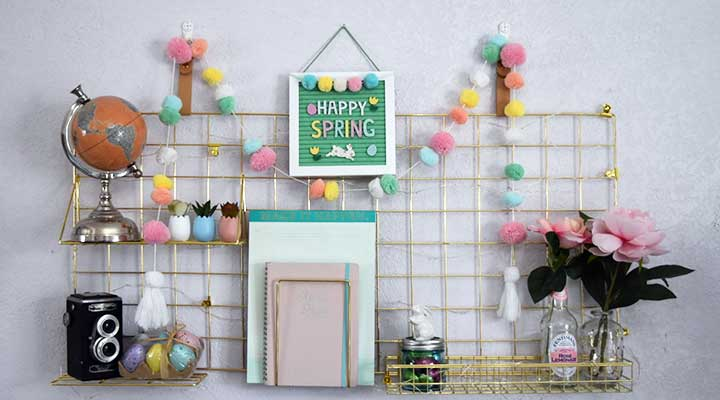 spring decor garland and spring eggs held up by metal wall organizer grid