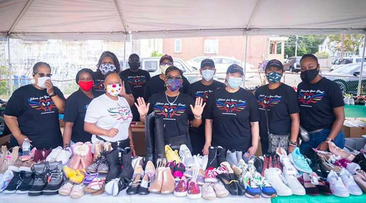 Shoes for Your Soul volunteers wearing face masks as a donation drive with rows of shoes on table