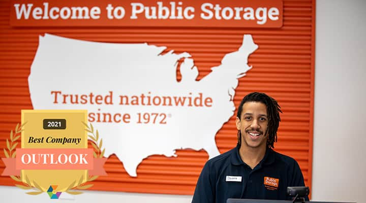 public storage employee smiles behind counter with welcome to public storage sign behind him