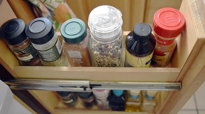 an open space between appliance opens to reveal a rack to organize spices