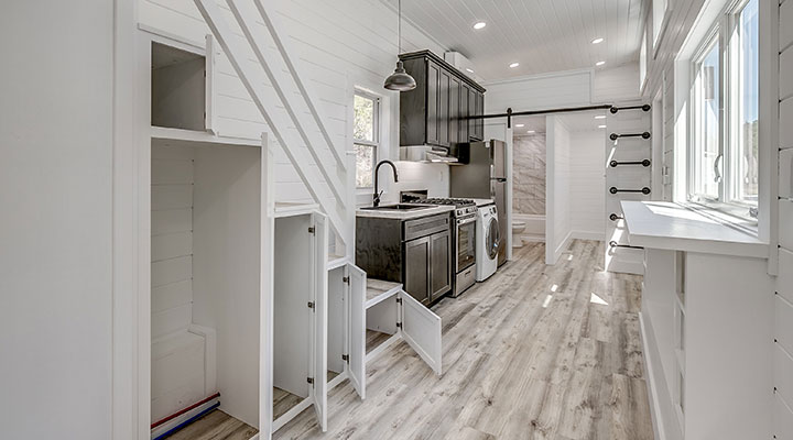view of a tiny home kitchen with white cabinets
