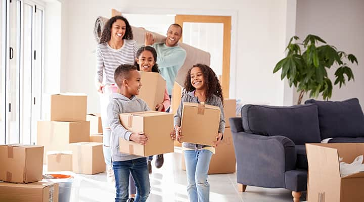 young family moving in boxes to new home