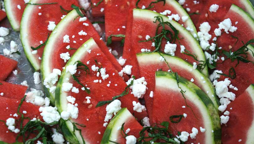 close up of watermelon wedges with basil and feta on a tray