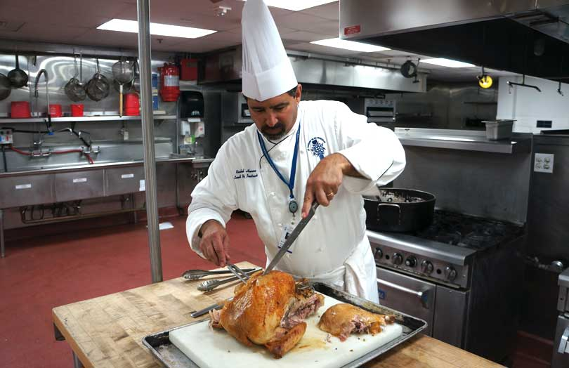chef demonstrates deboning a turkey cutting all the breast off at once