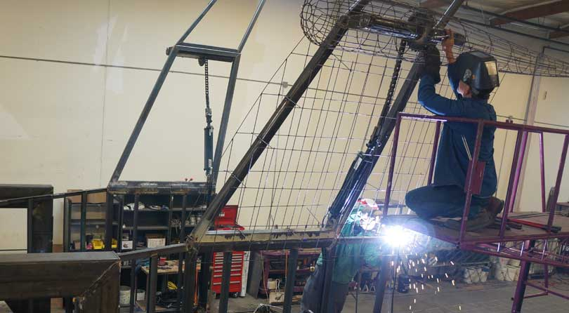a welder works on the frame for the public storage float